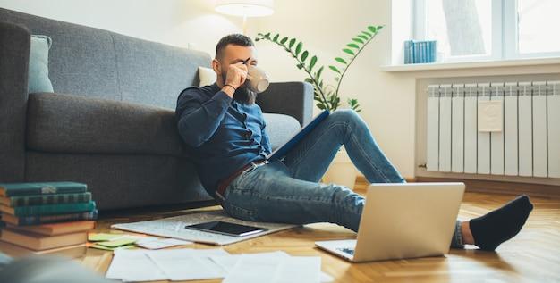 Der kaukasische geschäftsmann arbeitet mit einigen dokumenten, während er auf dem boden sitzt und einen kaffee trinkt