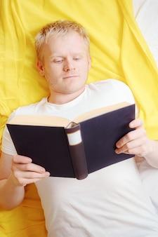 Der kaukasische junge kühle blonde mann in einem weißen t-shirt liest ein buch, während er sich hinlegt.