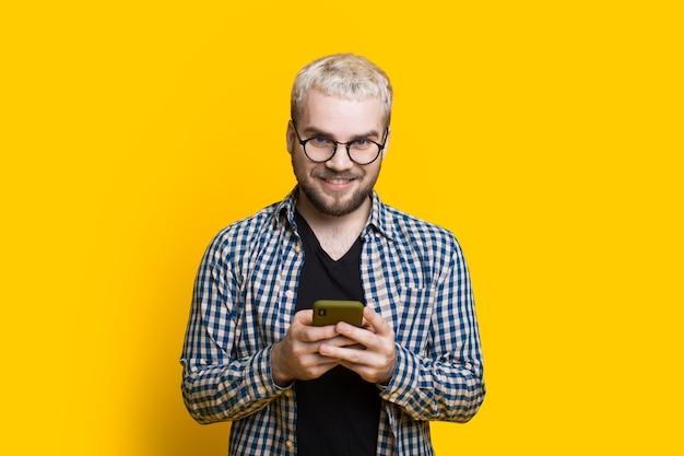Der kaukasische junge mit blonden haaren und brillen plaudert weiß mit jemandem auf einer gelben wand