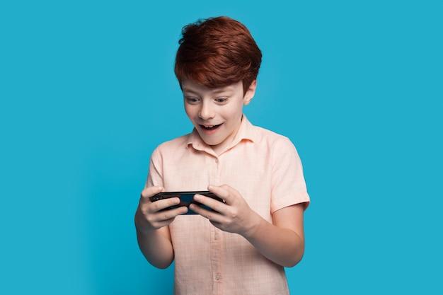 Der kaukasische junge posiert überrascht, während er videospiel auf dem handy auf einer blauen studiowand spielt