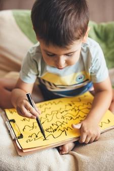 Der kaukasische kleine junge zeichnet auf einem gelben papier unter verwendung eines markers, während er am kindertag im bett sitzt