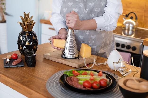 Der kaukasische kocher reibt käse für verschiedene gerichte auf dem tisch