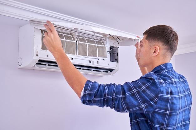 Der kaukasische männliche meister im blauen hemd reinigt filter, installiert und repariert klimaanlage in innenräumen