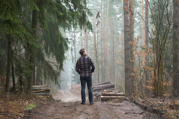 Der kaukasische mann hat einen spaziergang im nebligen wald