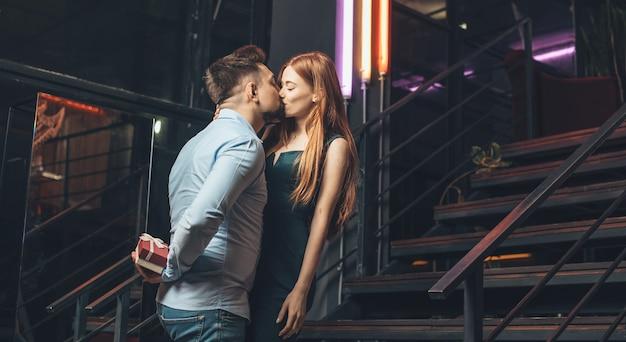 Der kaukasische mann küsst seine freundin und versteckt ein geschenk hinter seinem rücken