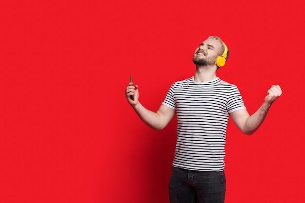 Der kaukasische mann mit bart und blonden haaren zeigt einen gewinn, während er musik auf einer roten wand mit freiem raum hört