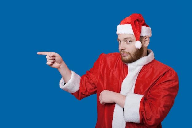 Der kaukasische mann mit bart und rotem haar, der weihnachtsmannkleidung trägt, zeigt auf etwas auf blauer wand mit freiem raum