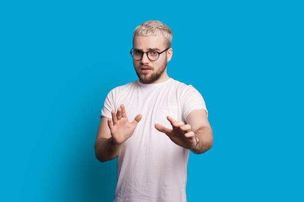 Der kaukasische mann mit brille und blonden haaren deutet auf eine blaue wand