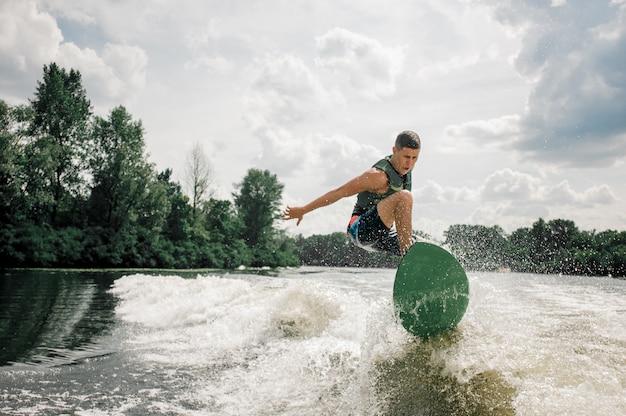 Der kaukasische mann reitet die wellen durch stilvolles wakeboard