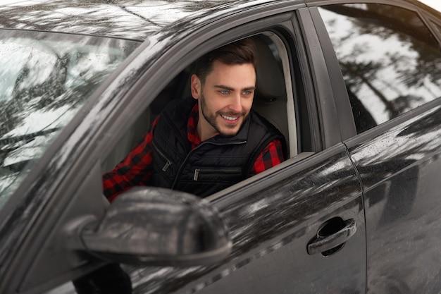 Der kaukasische mann sitzt am steuer seines autos