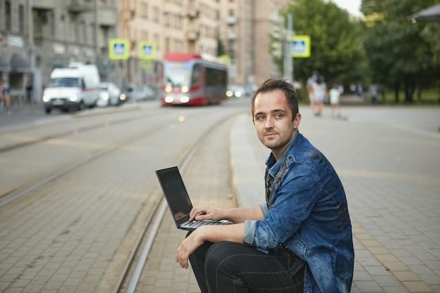 Der kaukasische mann sitzt gefährlich nahe an der eisenbahnstrecke mit notizbuch, während er auf das fahren der straßenbahn wartet.