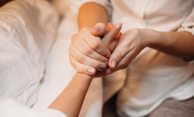 Der kaukasische masseur massiert die hand des kunden und bereitet sie auf das nächste spa-verfahren vor
