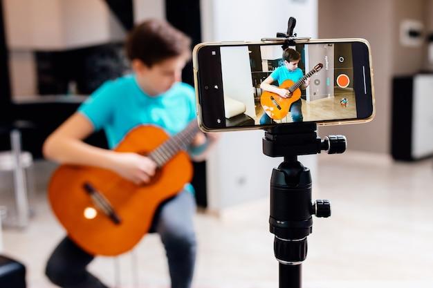 Der kaukasische teenager spielt gitarre und nimmt auf video auf