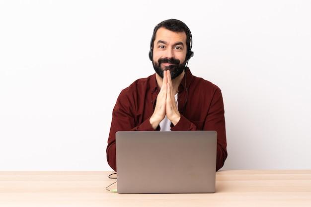 Der kaukasische telemarketer, der mit einem headset und mit laptop arbeitet, hält handfläche zusammen. person fragt nach etwas.