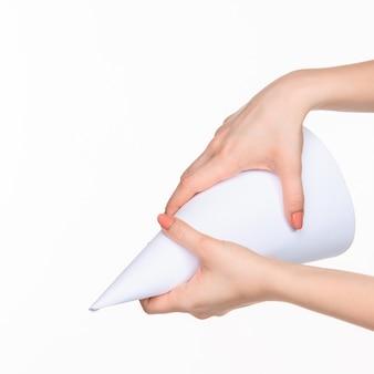 Der kegel in den weiblichen händen auf weißem hintergrund