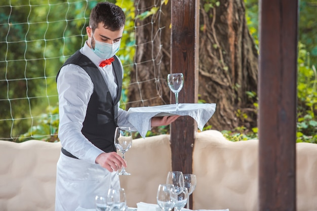 Der kellner arbeitet in einem restaurant auf der sommerterrasse