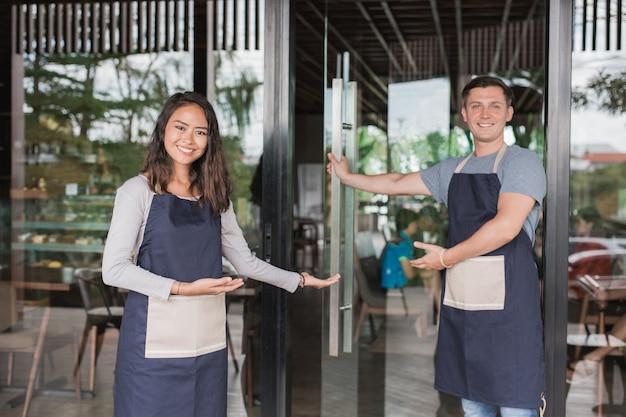 Der kellner begrüßt den kunden in seinem neu eröffneten café