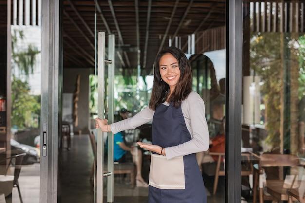 Der kellner begrüßt die kundin in ihrem neu eröffneten café