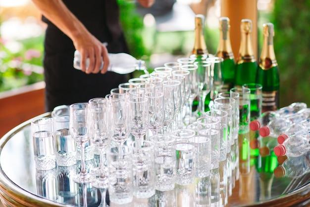 Der kellner gießt champagner auf den buffettisch.