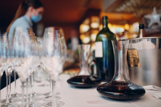 Der kellner gießt elite-rotwein in die karaffe auf dem tisch im restaurant.