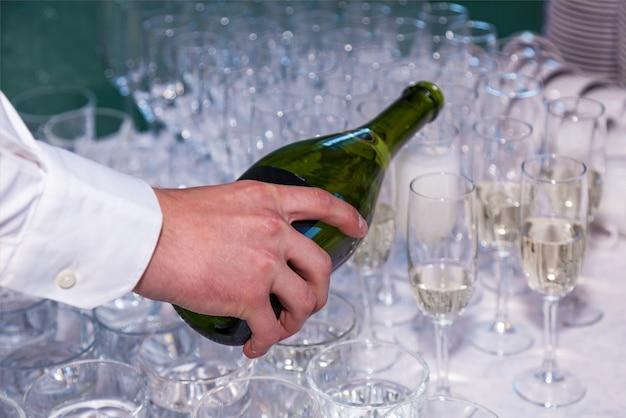 Der kellner gießt in einem restaurant champagner aus einer flasche in gläser. catering, bankett