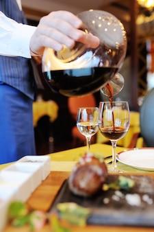Der kellner gießt rotwein aus einer schönen flasche vor dem hintergrund des restaurants und des essens