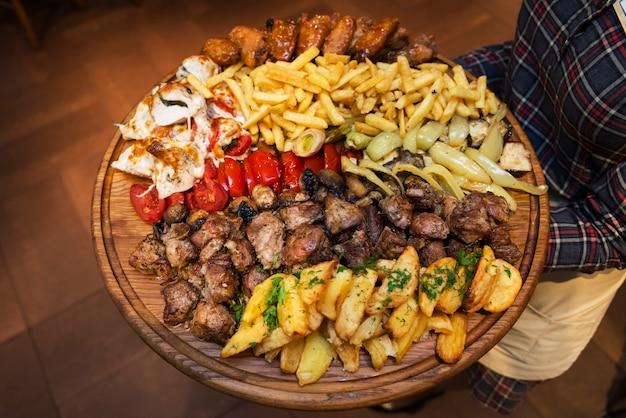 Der kellner hält ein großes brett mit einer köstlich zubereiteten auswahl an fleisch und gemüse