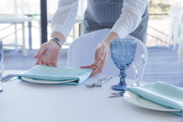 Der kellner im restaurant serviert einen tisch für eine hochzeitsfeier