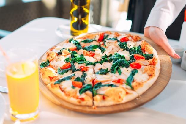 Der kellner legt pizza auf den tisch im restaurant.