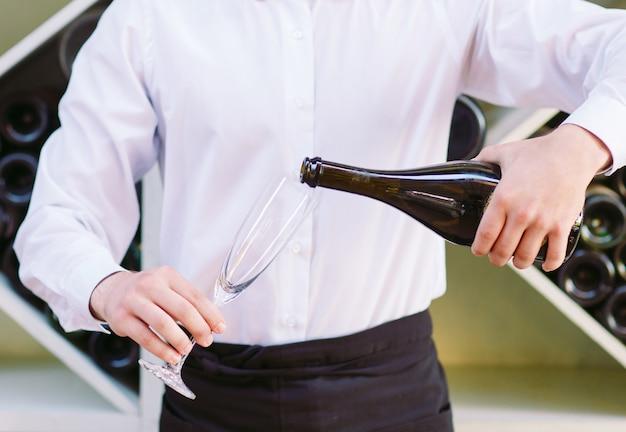 Der kellner verschüttet den champagner.