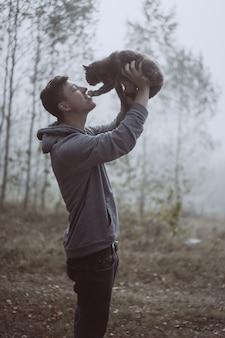 Der kerl hält eine katze im park. der park ist in nebel gehüllt