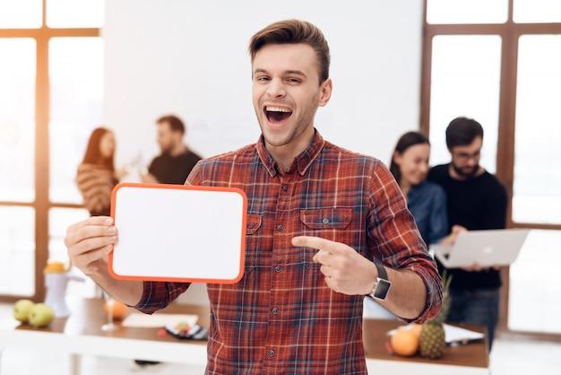 Der kerl hält eine weiße tafel in der hand.