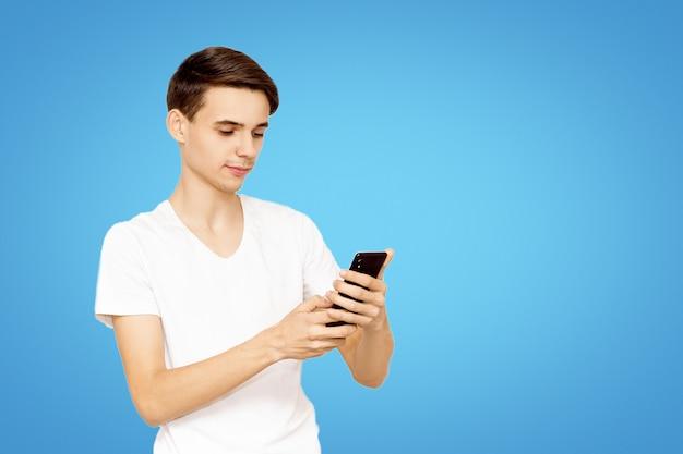Der kerl im weißen t-shirt mit dem telefon auf einem blauen hintergrund. junger teenager in sozialen netzwerken, das konzept der modernen technologie vorgeschrieben