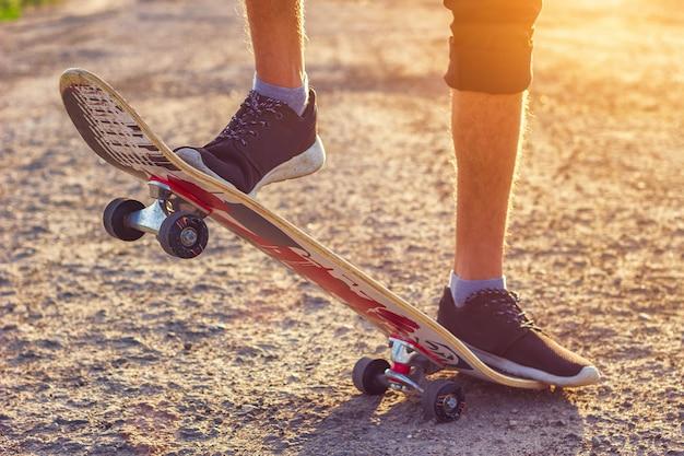Der kerl steht auf einem skateboard ist auf der straße schön straffend.
