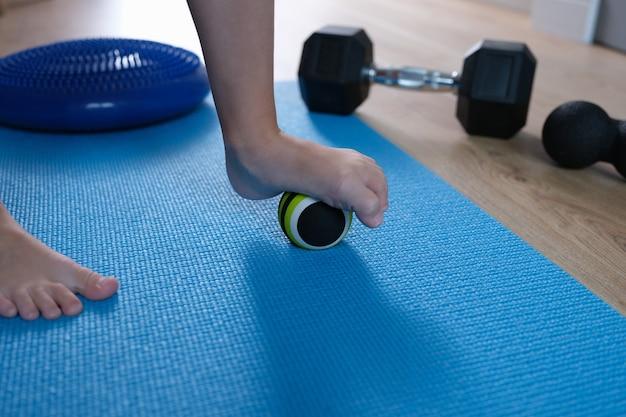 Der kinderfuß ruht auf einem kleinen gymnastikball, um die füße zu massieren. massageballspiele und übungen