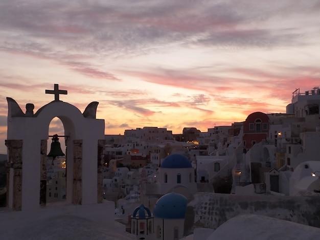Der kirchenglocketurm gegen pastellfarbabendhimmel in oia-dorf, santorini-insel, griechenland