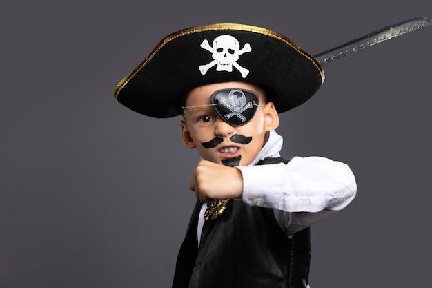 Der klassische piratenkapitän, der einen säbel schwingt. halloween-feiertagskonzept auf grauer wand.