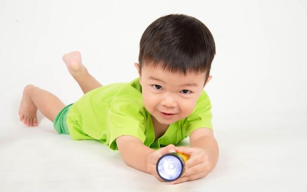 Der kleine asiatische kleinkindjunge, der hölzerne blöcke spielt, tragen sturzhelmingenieur