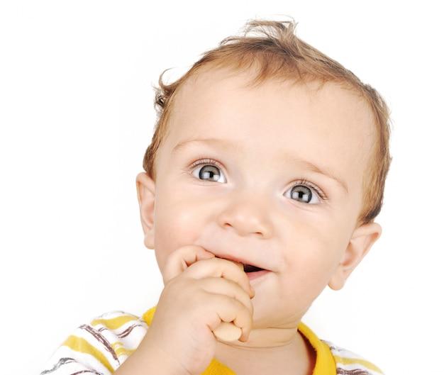 Der kleine junge beißt holzspielzeug