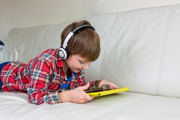 Der kleine junge, der auf bett legt, spielen die tablette