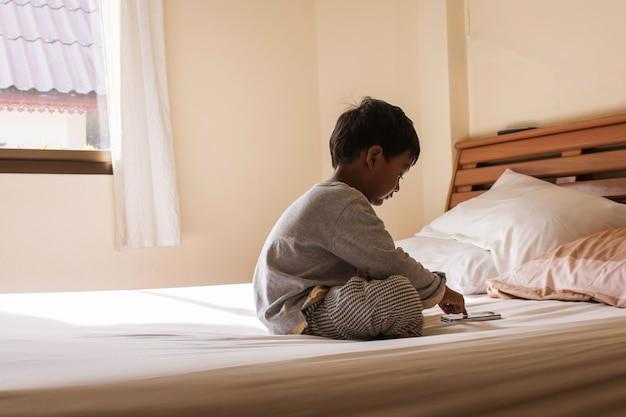 Der kleine junge, der auf bett sitzt, spielt intelligentes telefon im schlafzimmer