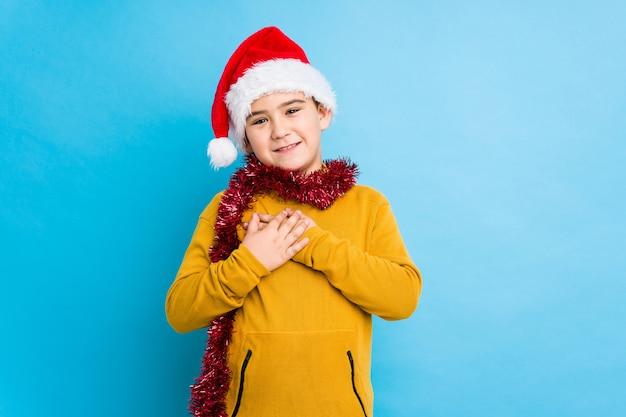 Der kleine junge, der den weihnachtstag lokalisiert trägt einen sankt-hut feiert, hat den freundlichen ausdruck und drückt palme zum kasten. liebes-konzept.