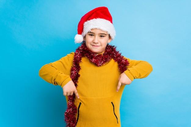 Der kleine junge, der den weihnachtstag lokalisiert trägt einen sankt-hut feiert, zeigt unten mit den fingern, positives gefühl.