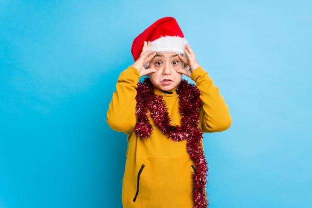 Der kleine junge, der den weihnachtstag trägt einen sankt-hut feiert, lokalisierte das halten von augen, die geöffnet wurden, um eine erfolgschance zu finden.