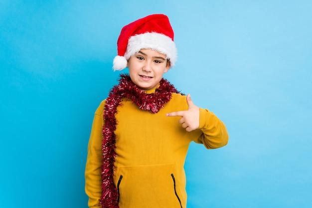 Der kleine junge, der den weihnachtstag trägt einen sankt-hut feiert, lokalisierte die person, die eigenhändig auf einen hemdkopienraum zeigt, der stolz und überzeugt ist
