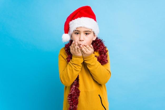 Der kleine junge, der den weihnachtstag trägt einen sankt-hut feiert, lokalisierte faltende lippen und das halten von palmen, um luftkuss zu senden.