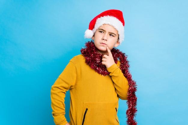 Der kleine junge, der den weihnachtstag trägt einen sankt-hut feiert, lokalisierte mit zweifelhaftem und skeptischem ausdruck seitlich schauen.