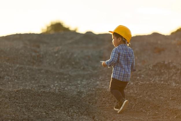 Der kleine junge, der einen sturzhelm, traumkonzept trägt, möchte ein zukünftiger ingenieur sein.