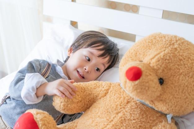 Der kleine junge, der mit großem teddybären spielt, betreffen bett