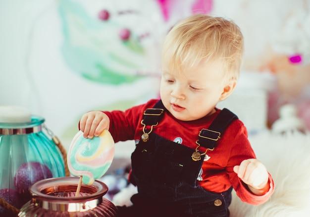 Der kleine junge, der mit vasen mit bonbons spielt